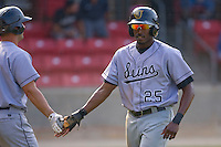 Gregory Burns #25 of the Jacksonville Suns is congratulated by a teammate after scoring a run against the Carolina Mudcats at Five County Stadium May 16, 2010, in Zebulon, North Carolina.  Photo by Brian Westerholt /  Seam Images