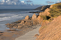 Sandymouth Beach lies 3 miles north of Bude on the North Cornwall coast, to which it is joined by a long sandy beach at low tide. It is owned by the National Trust and is a popular lifeguarded beach in summer. At low tide a vast tract of sand is uncovered, making it one of the longest beaches in Cornwall. At high tide only the pebbles remain. In winter, when this shot was taken, it is virtually deserted. It is my favourite beach in our area and I have photographed it many times. This shot was taken from the cliffs to the south, on the way to Northcott Mouth and shows its attractive rock formations and waterfall, bathed in late afternoon light just prior to sunset. Lower Sharpnose Point is the headland in the background.