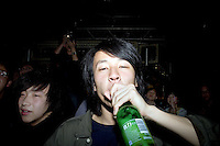 An audience member drinks beer from a bottle during a punk concert at Castle Bar in Nanjing, China.