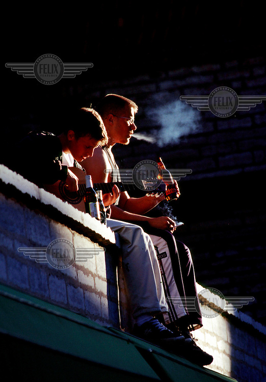 Youths sitting on a wall in the Old Town, drinking beer and smoking cigarettes, on a sunny summer evening.