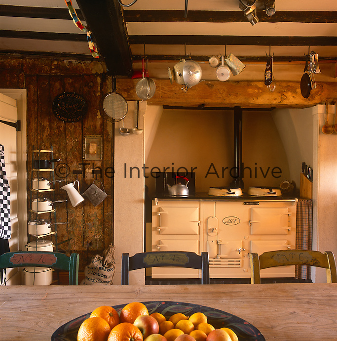 A traditional, country kitchen with a beamed ceiling and an Aga in a recess.