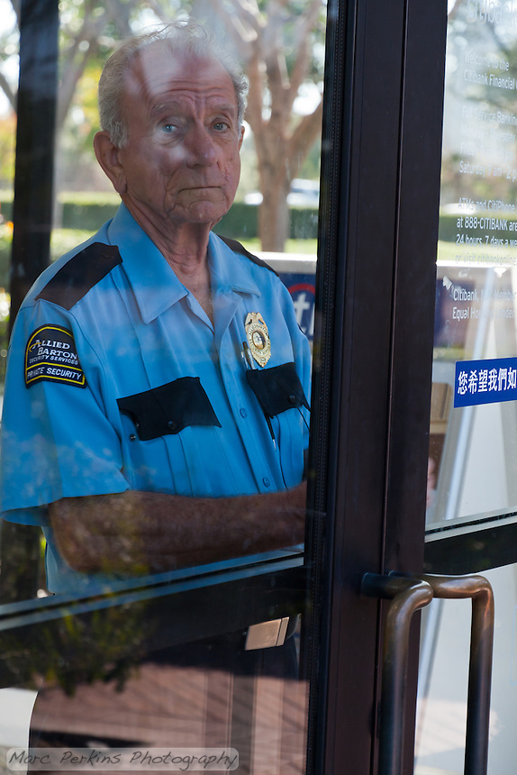 Charles, a security guard at a Citibank branch in Irvine, CA, warily watches through a locked door as protesters from the Occupy Orange County, Irvine camp march in front of his bank on November 5.
