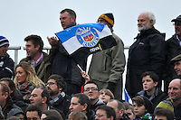 A Bath fan in the crowd waves a flag in support. LV= Cup match, between Bath Rugby and Exeter Chiefs on November 17, 2013 at the Recreation Ground in Bath, England. Photo by: Patrick Khachfe / Onside Images