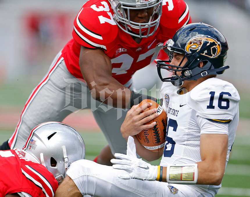Ohio State Buckeyes linebacker Raekwon McMillan (5) and Ohio State Buckeyes linebacker Joshua Perry (37) sack Kent State Golden Flashes quarterback Nathan Strock (16) in the 2nd quarter of their game in Ohio Stadium on September 13, 2014.  (Dispatch photo by Kyle Robertson)