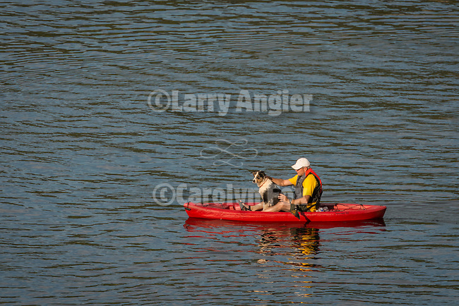A man in a red kayak takes his dog for a ride across Lower Bear River Reservoir in the El Dorado National Forest, Amador County, Calif.