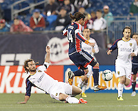 New England Revolution midfielder Lee Nguyen (24) eludes Real Salt Lake midfielder Kyle Beckerman (5) slide tackle. In a Major League Soccer (MLS) match, Real Salt Lake (white)defeated the New England Revolution (blue), 2-1, at Gillette Stadium on May 8, 2013.