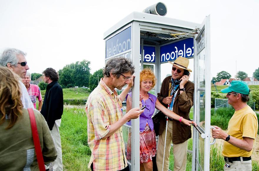 Nederland, Edam, 5 juli  2009.www.eendijkvaneenkust.nl.Hannes Wallrafen in een telefooncel waar zijn geluidsproject te horen is..Foto (c) Michiel Wijnbergh