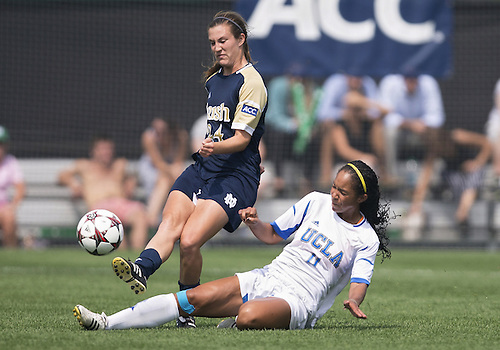 September 01, 2013:  Notre Dame defender Katie Naughton (24) kicks the ball upfield as UCLA forward Darian Jenkins (11) attempts slide tackle during NCAA Soccer match between the Notre Dame Fighting Irish and the UCLA Bruins at Alumni Stadium in South Bend, Indiana.  UCLA defeated Notre Dame 1-0.