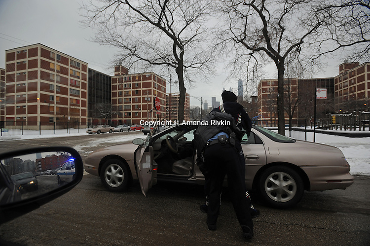 A young, black male is stopped and frisked by a Chicago police officer in an unmarked car in the Cabrini Green housing project in Chicago, Illinois on February 8, 2008.