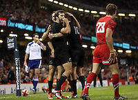 Pictured: Beauden Barrett of New Zealand is mobbed by team mates celebrating his try who mock Liam Williams of Wales (R) Saturday 22 November 2014<br />