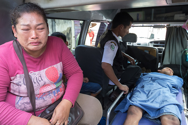 """5 April 2017, Surabaya,East Java,Indonesia: Febrianto, a 24 year old mental illness sufferer is placed in an ambulance in a strait jacket after his release from the chains he has been shackled to a stake for the past two years in a goat shed next to his family in Pehwetan village, East Java. Indonesian as his mother Barokah, looks on. Social Affairs Dept. workers cut the bonds and washed his emaciated body and apply first aid before putting him in an ambulance and taking him to a facility in Malang for treatment. Febrianto is a patient in a program called """"E- Shackling"""" which aims to free people suffering from mental illness, from the shackles that family often place them in to control them in the wake of a lack of treatment options and which will treat them and enter them in a data base allowing them to be traced before releasing them back to their families. Some people stay chained to a stake or in rooms for years by their families and not all families are willing to take their sick family members back. Picture by Graham Crouch/The Australian"""