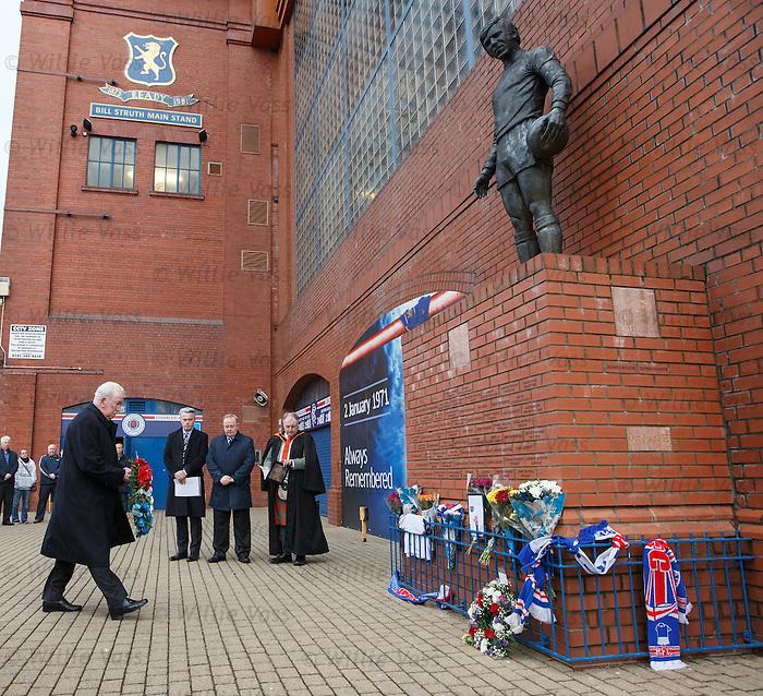 John Greig walks up to lay a wreath at the memorial statue at Ibrox Stadium