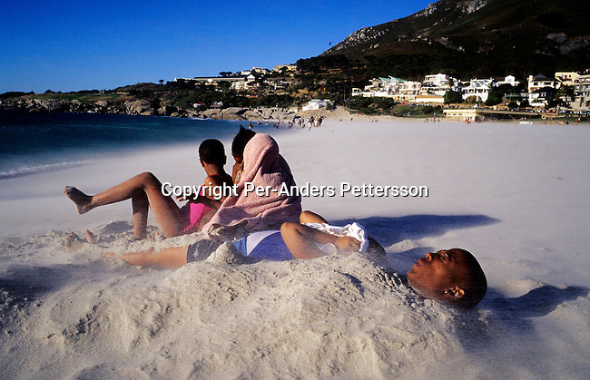 CAMPS BAY, SOUTH AFRICA - JANUARY 1: Unidentified holidaymakers take cover during a sand storm as the sun sets on January 1, 2003 in Camps Bay outside Cape Town, South Africa. Camps Bay has some of the best beaches and most expensive properties in the country, and it?s a popular place for locals and foreign visitors. .(Photo: Per-Anders Pettersson/Getty Images)........