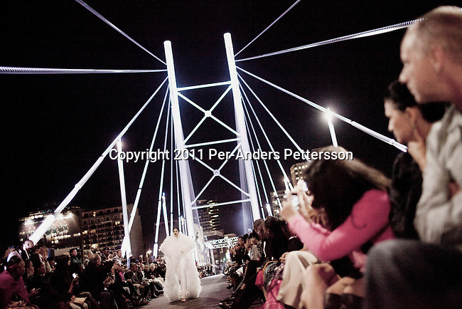 JOHANNESBURG, SOUTH AFRICA - FEBRUARY 19: A model walks for the designer David Tlale on the Nelson Mandela Bridge at the Joburg Fashion Week on February 19 2011, in Johannesburg, South Africa. David Tlale, is an award winning designer and one of South Africa's finest designers, dressing celebrities and others in couture with elegance and high quality material. He held his show at the Mandela Bridge in downtown Johannesburg. A logistical nightmare, the bridge was closed and turned into a  catwalk at midnight with hundreds of people watching the show. 92 models, one for each of Nelson Mandela's years walked the 285 meter bridge, maybe the longest catwalk in the world. South African top designers with showed their 2011 Autumn & Winter collections during the 5 day event. (Photo by Per-Anders Pettersson)
