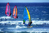 Three windsurfers at Backyards Sunset Beach, Oahu
