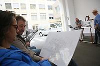Besucher betrachten im Rahmen des Vortrags historische Fotografien und Pläne des Werks