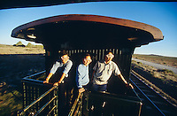 Rovos Rail. Railway buffs wearing safety goggles on a Royal Suite car?s platform, while the train is steam-hauled through the Karoo.