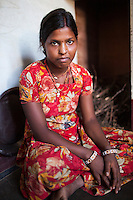 Nitu (not her real name), sits in her kitchen in Jhaju village, Bikaner, Rajasthan, India on 4th October 2012. Now 18, she was married off at age 10 to a boy of around the same age, but only went to live with her in-laws when she was 12, after she had finished studying up to class 6. The three sisters, aged 10, 12, and 15 were married off on the same day by their maternal grandfather while their father was hospitalized. She was abused by her young husband and in-laws so her father took her back after hearing that her husband, who works in a brick kiln, was an alcoholic and was doing drugs and crime. She had only spent a few days at her husband's house at that time. Her father (now out of the hospital) has said that she will only be allowed to return to her husband's house if he changes his ways but so far, the negotiations are still underway. Photo by Suzanne Lee for PLAN UK