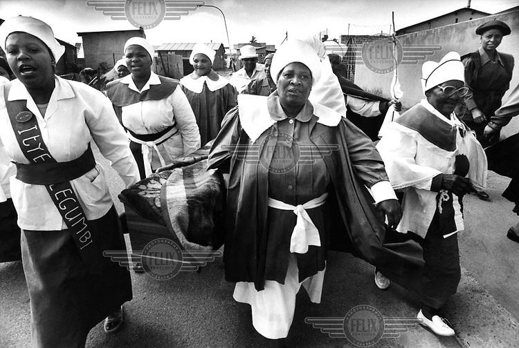 © Dieter Telemans / Panos Pictures..Gospel, South-Africa, Zuid-Afrika, december 2000..Funeral of grandma Nkosi Nomasonto (64) in Soweto. Members of the Zion Christian Church carry the coffin from her home towards the undertakers car...Begrafenis van grootmoeder Nkosi Nomasonto (64) in Soweto. Leden van Zion Christian Church dragen de kist van haar huis naar de lijkwagen. ..Trefw. : geloof, religie, zingen, begrafenis, doodskistPhoto:  Dieter Telemans / Panos Pictures/Felix Features