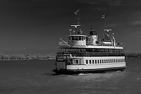 A black and white view of the Ward's Island ferry crossing the Toronto harbour with the Islands in the background
