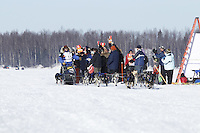 A crowd of spectators gives Martin Buser a round of applause as he passes by on Long Lake in Willow, Alaska duirng the re-start of the 2011 Iditarod.