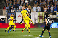 Eddie Gaven (12) of the Columbus Crew goes up for a header with Gabriel Farfan (15) of the Philadelphia Union. The Columbus Crew defeated the Philadelphia Union 2-1 during a Major League Soccer (MLS) match at PPL Park in Chester, PA, on August 29, 2012.
