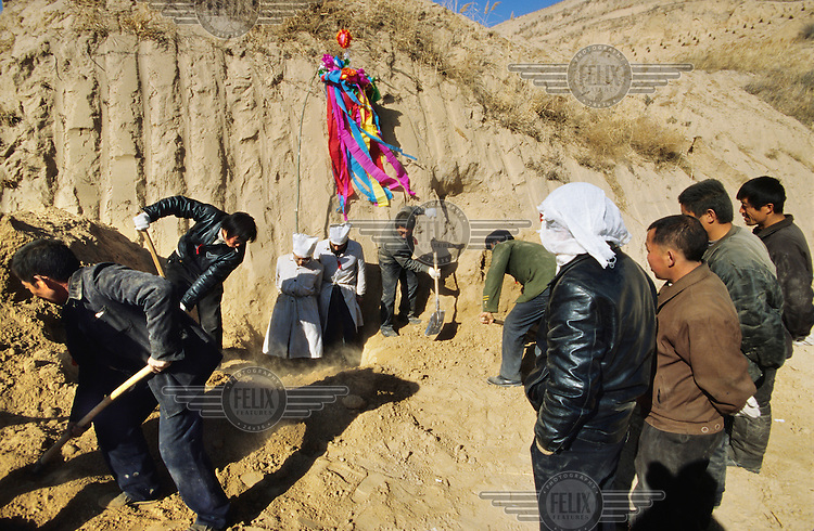 Men dig the soil in preparation for a funeral service on a hilltop in the in the Loess Plateau.  The plateau is located in one of China's driest regions and experiences extensive soil erosion..
