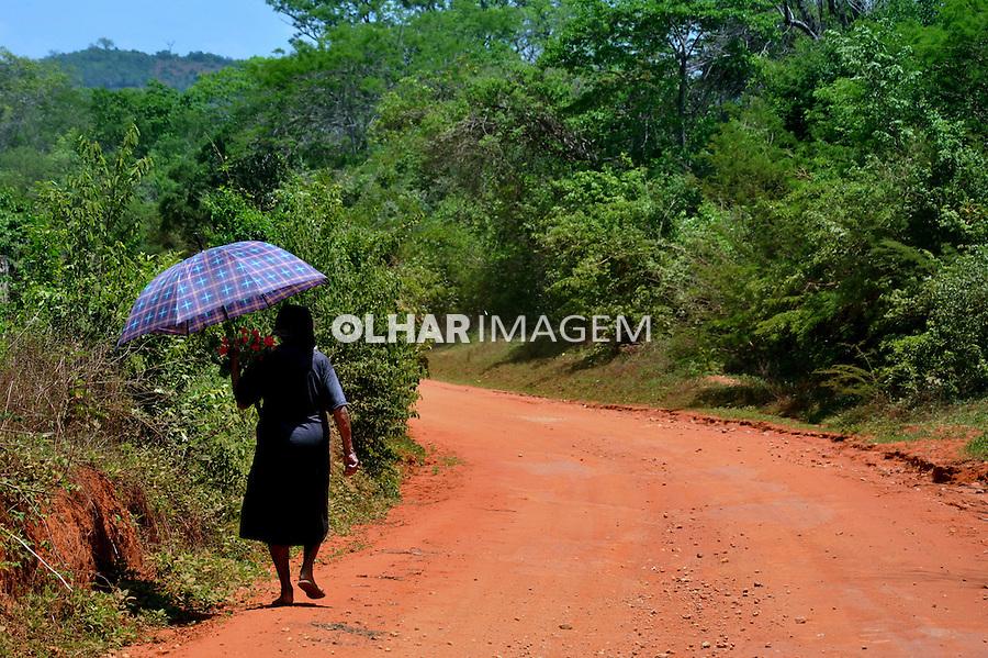 Mulher caminhando em estrada de terra na caatinga. Tremedal. Bahia. 2012. Foto de Alberto Viana.