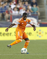Houston Dynamo defender Kofi Sarkodie (8) passes the ball.  In a Major League Soccer (MLS) match, Houston Dynamo (orange) defeated the New England Revolution (blue), 2-1, at Gillette Stadium on July 13, 2013.