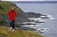 Woman on bluff overlooking rugged Atlantic Ocean coastline, Cape Onion, Newfoundland, Canada