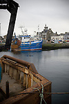 Trawlers at berth in the harbour at Fraserburgh, Aberdeenshire, with the floodlights Bellslea Park, home of Fraserburgh FC, visible in the background. Nicknamed 'The Broch,' the club have been members of the Highland League since 1921 having been formed 11 years earlier.