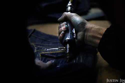 "A worker drills a pair of jeans in Mr Huang's factory in Zhongshan city, China..This picture is part of a photo and text story on blue jeans production in China by Justin Jin. .China, the ""factory of the world"", is now also the major producer for blue jeans. To meet production demand, thousands of workers sweat through the night scrubbing, spraying and tearing trousers to create their rugged look. .At dawn, workers bundle the garment off to another factory for packaging and shipping around the world..The workers are among the 200 million migrant labourers criss-crossing China.looking for a better life, at the same time building their country into a.mighty industrial power."