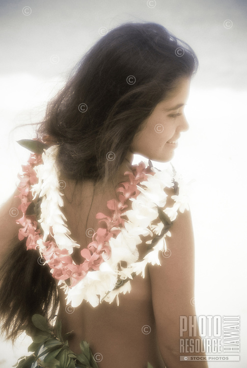 Polynesian woman at the beach with flower leis draped along her back