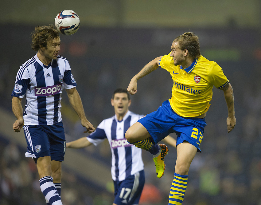 West Bromwich Albion's Diego Lugano heads clear from Arsenal's Nicklas Bendtner<br /> <br /> Photo by Stephen White/CameraSport<br /> <br /> Football - Capital One Cup Third Round - West Bromwich Albion v Arsenal - Wednesday 25th September 2013 - The Hawthorns - West Bromwich<br />  <br /> &copy; CameraSport - 43 Linden Ave. Countesthorpe. Leicester. England. LE8 5PG - Tel: +44 (0) 116 277 4147 - admin@camerasport.com - www.camerasport.com