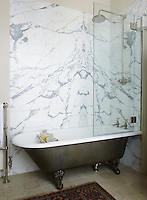 In the bathroom the traditional free-standing bath with claw and ball feet has an overhead shower.