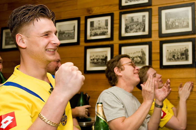 Ukraine fan Philip Bogachuk cheers on his team during a World Cup match against Saudi Arabia on June 19, 2006 at the Ukrainian Sports Club in New York City.<br /> <br /> The World Cup, held every four years in different locales, is the world's pre-eminent sports tournament in the world's most popular sport, soccer (or football, as most of the world calls it).  Qualification for the World Cup is open to any country with a national team accredited by FIFA, world soccer's governing body. The first World Cup, organized by FIFA in response to the popularity of the first Olympic Games' soccer tournaments, was held in 1930 in Uruguay and was participated in by 13 nations.    <br /> <br /> As of 2010 there are 208 such teams.  The final field of the World Cup is narrowed down to 32 national teams in the three years preceding the tournament, with each region of the world allotted a specific number of spots.  <br /> <br /> The World Cup is the most widely regularly watched event in the world, with soccer teams being a source of national pride.  In most nations, the whole country is at a standstill when their team is playing in the tournament, everyone's eyes glued to their televisions or their ears to the radio, to see if their team will prevail.  While the United States in general is a conspicuous exception to the grip of World Cup fever there is one city that is a rather large exception to that rule.  In New York City, the most diverse city in a nation of immigrants, the melting pot that is America is on full display as fans of all nations gather in all possible venues to watch their teams and celebrate where they have come from.