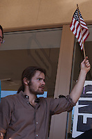 Dan waves an American flag underneath the Bank of America sign (reflected in the window) during the Occupy Orange County, Irvine march on November 5.