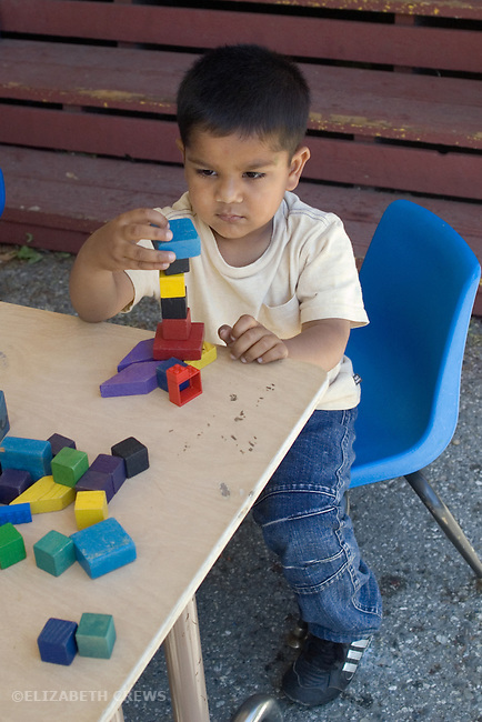 Berkeley CA  Four-year-old concentrating on block construction in solitary play at preschool