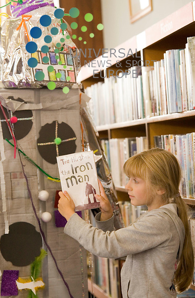 Seven year old Caitlin Gamble at Knightswood Library Glasgow, with a human-sized Iron Man made from junk by the children, the Iron Man is from the Ted Hughs childrens book of the same name..Picture/Johnny mclauchlan/Universal news and sport(scotland)14/07/2009