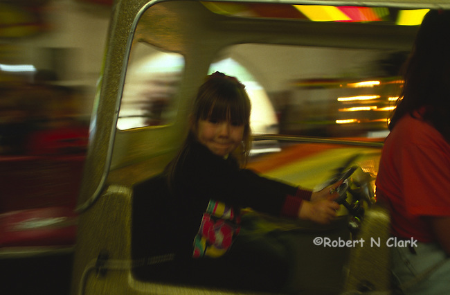 Girl in driver's seat of ride at fair zooming past camera showing blur os speed