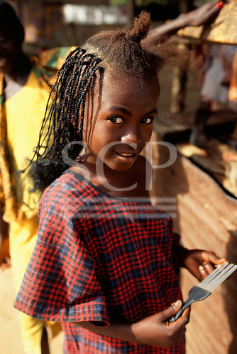 Gambia. Girl with plaited hair holding an afro comb.