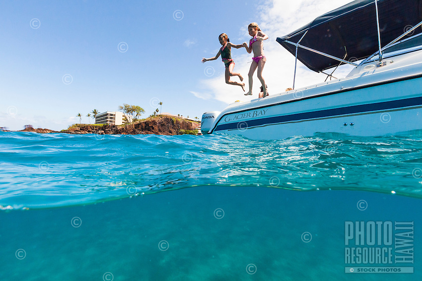 Split-level view of two girls happily jumping from a boat into the clear ocean water, Maui.
