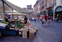 Mantova, mercato in Piazza delle Erbe, gente in bicicletta.<br /> Mantua, the market in Piazza delle Erbe, people on bicycles.