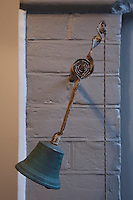 An antique bell with rusting spring mounted on the wall of the porch