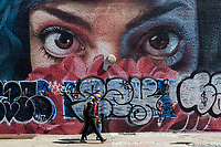 NEW YORK, NY - April 14: Two men wearing face masks cross in front of graffiti on April 14, 2020 in Brooklyn, NY. The global number of deaths from COVID-19 has reached 122,000 and infected more than 1.9 million people. Experts believe the number may be greater. (Photo by Pablo Monsalve / VIEWpress via Getty Images)