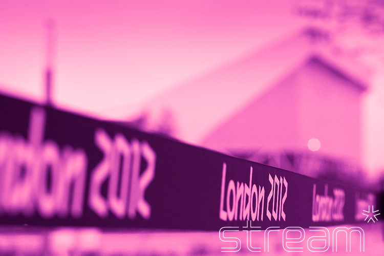 A 'London 2012' sign in focus with Aquatics Centre (blurred) in background. Pink tinted image.
