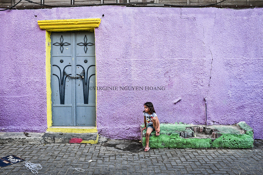 GAZA, Zaytoun: a girl is resting in  her street totally painted. The initiative of Mohammed Al Saedy was aided by the Tamer Institute for Community Education, a Palestinian nonprofit that contributed organisation with painting supplies.  15/08/15<br /> <br /> GAZA , Zaytoun : une jeune fille se repose dans sa rue enti&egrave;rement peinte . L'initiative de Mohammed Al Saedy a &eacute;t&eacute; aid&eacute;e par l'Institut Tamer pour l'&eacute;ducation communautaire, une organisation palestinienne &agrave; but non lucratif  qui a contribu&eacute; &agrave; fournir la peinture. 15/08/15