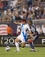 Puebla FC forward Gabriel Pereyra (8) attempts to control the ball as New England Revolution defender Darrius Barnes (25) pressures. The New England Revolution defeated Puebla FC in penalty kicks, in SuperLiga 2010 semifinal at Gillette Stadium on August 4, 2010.
