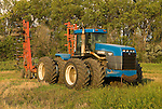 1990s Blue Ford (Veritile) 8-wheel tractor, model 9680 with chisel plow at edge of a field
