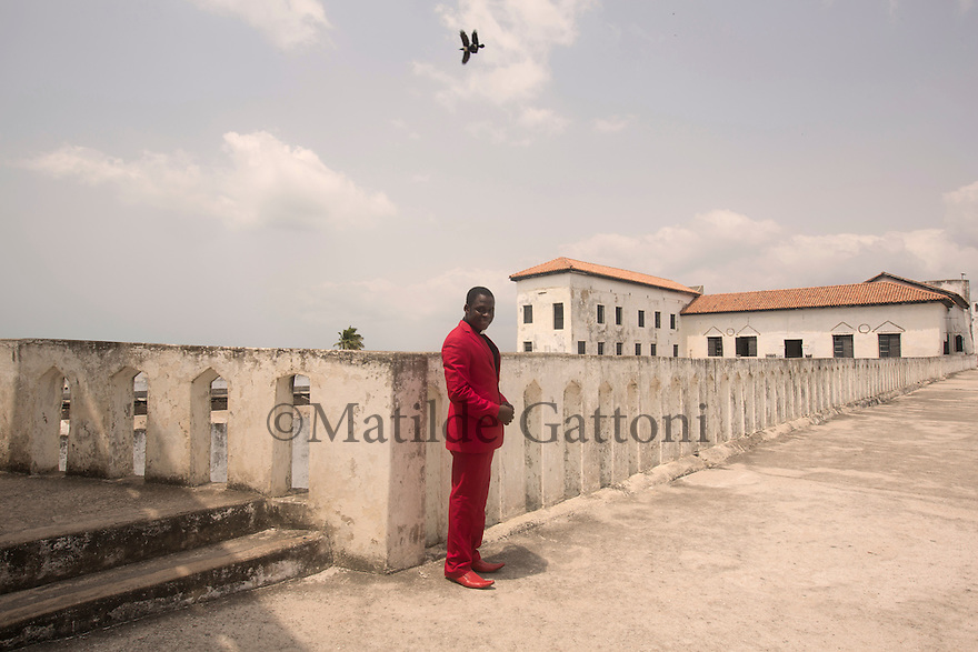 "Ghana - El Mina - A local priest stands on the rooftop of the castle. A UNESCO World Heritage Site, the Castle of Elmina was built by the Portuguese in 1487 and was the first ""slave fort"" to be erected along the West Africa coast. Today, the Elmina coast is threatened by coastal erosion, mostly due to uncontrolled sand mining which has permanently damaged the town's beaches."